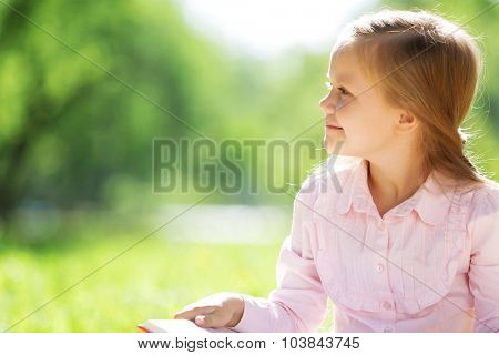 Child with book having picnic in summer park