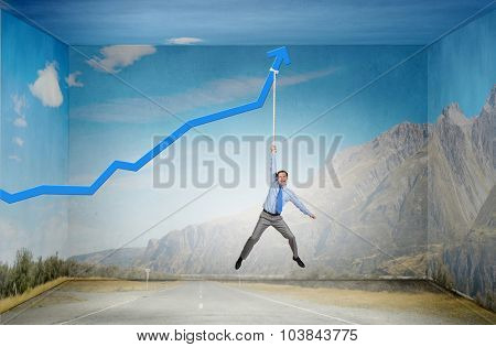 Young businessman hanging on increasing blue graph
