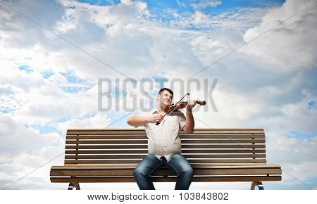 Fat man sitting on bench and playing violin