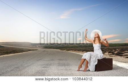 Woman in white long dress and hat sitting on her luggage on asphalt  road