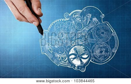Person hand drawing cogwheels mechanism on blue background