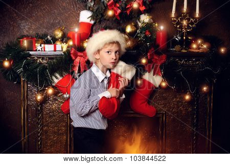 Cute seven year old boy stands with gifts by the fireplace at home. The magic of Christmas.