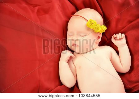 Beautiful little newborn girl lying on red blanket in lovely yellow headband with flowers.