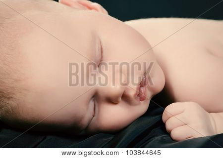 Close-up portrait of a sleeping sweet newborn baby. Over black background.
