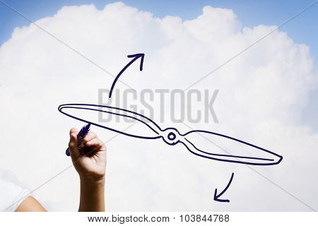 Person drawing plane propeller on sky background