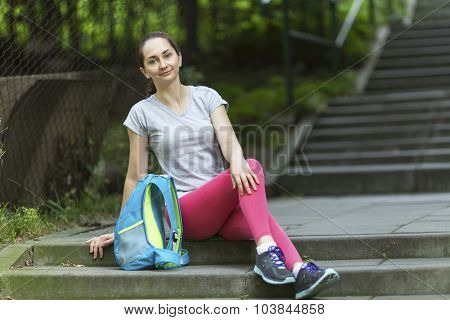 Young sporty girl sitting on the steps of the alley after a workout.