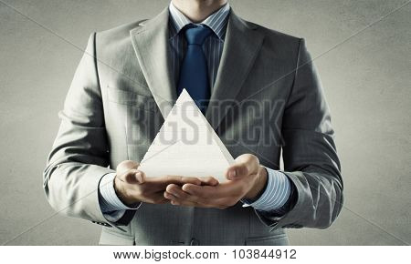 Close up of businessman holding pyramid in hands