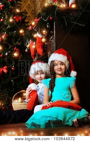 Two cute children in Santa hats holding gifts by the Christmas tree at home. The magic of Christmas.
