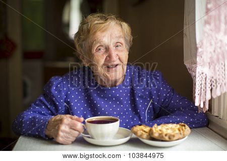 Grandmother, elderly woman, drinking tea sitting at the table in the house.
