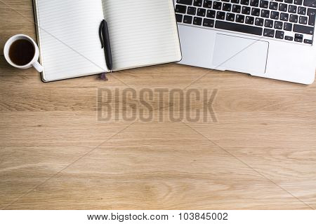 Notepad with pen, Cup of coffee and a laptop with the Eng/Russian keyboard layout, the texture of the wood, with space for text.