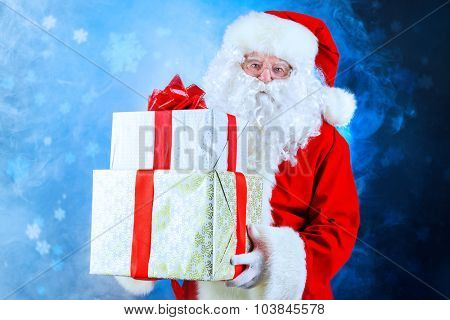 Portrait of Santa Claus holding gift boxes. Christmas time.