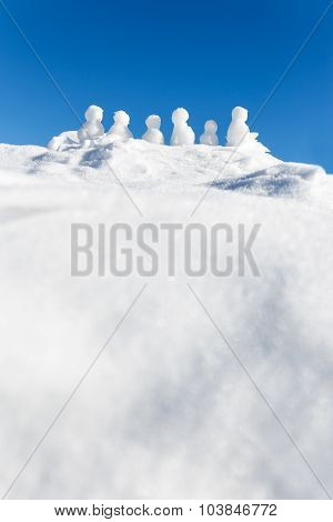 Little Snowmen Figures Standing On A Mountaintop, Copyspace In The Front
