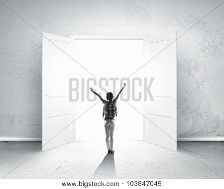 Rear view of woman with hands up entering opened door