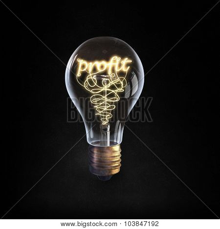 Glowing glass light bulb with word profit inside