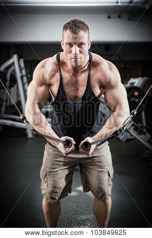 Bodybuilder doing butterfly on cable pull for better definition of his arm muscles