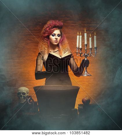 Beautiful witch casting a spell using a magical vat, a book and a candlestick. Halloween concept.