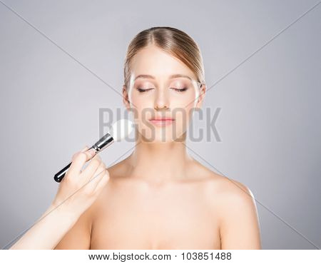 Beautiful girl is being applied with cosmetics.