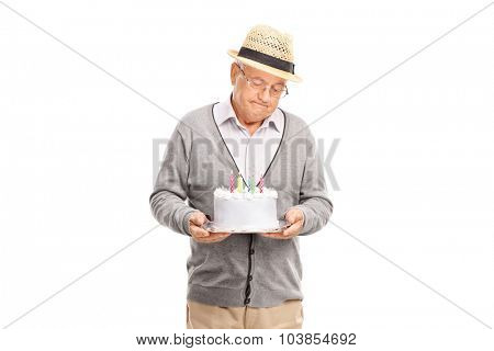 Studio shot of a lonely senior gentleman holding a birthday cake isolated on white background