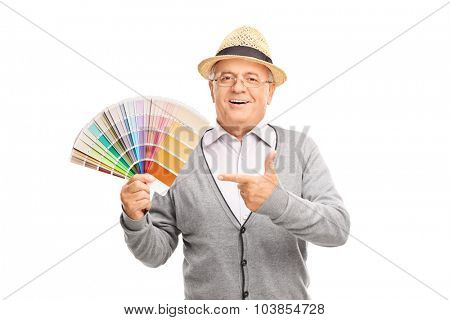 Senior gentleman holding a color palette guide in one hand and pointing towards it with the other isolated on white background