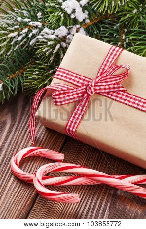 Christmas gift box, candy cane and tree branch on wooden table