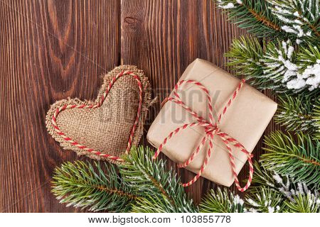 Christmas tree branch with snow, gift box and heart toy on wooden table. Top view