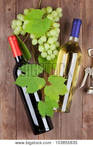 Bunch of grapes, wine bottles and corkscrew on wooden table background