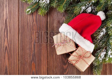 Christmas tree branch and santa hat with gift boxes on wooden table. Top view with copy space