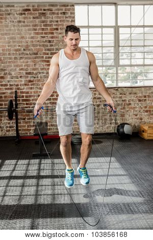 Muscular man doing skipping exercise at the gym