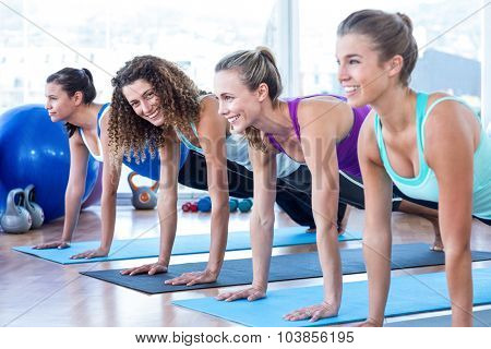 Portrait of woman with friends doing plank pose in fitness studio