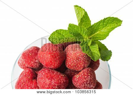Frozen strawberries and a sprig of fresh mint