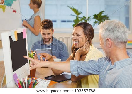 Businessman pointing on computer screen as happy female colleague looking at it with employees working in baackground