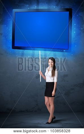 Young businesswoman holding a big, blue shining tablet