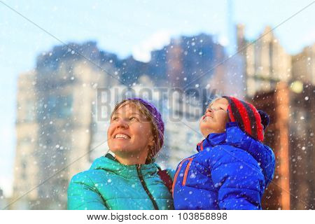 mother and son enjoy first snow in the city