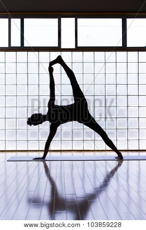Young woman practicing in a yoga studio. This is an advanced version of side plank pose or vasisthasana
