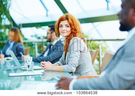 Pretty young businesswoman looking at camera during lecture