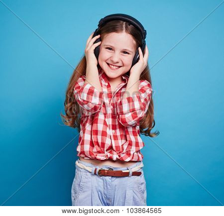 Pretty girl with headphones looking at camera and enjoying music