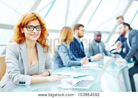 Pretty employee looking at camera in working environment