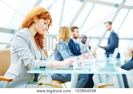 Pretty young businesswoman typing on laptop