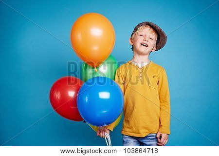 Little boy holding several multi-color balloons