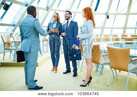 Happy managers in suits discussing morning news in office