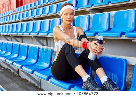 Fit young woman with container of water sitting at stadium