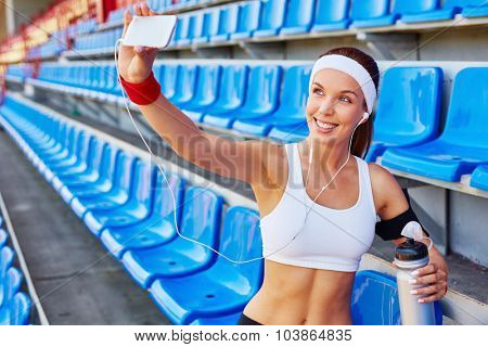 Active girl making her selfie at stadium