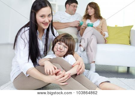 Two siblings sitting on the floor on background of their parents having tea