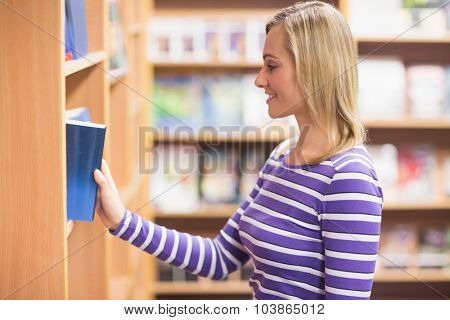 Side view of young woman selecting book from bookshelf in library