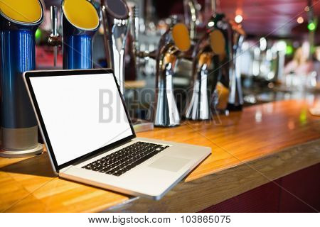 Laptop with blank screen on bar counter