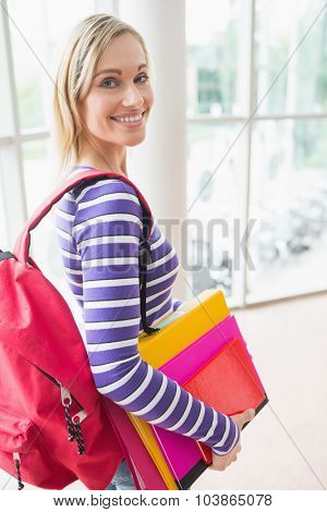 Close-up portrait of young female student with backpack and books in college