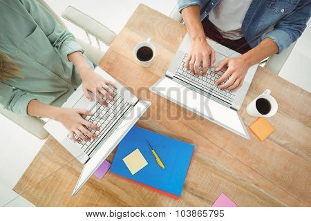 Midsection of man and woman using laptop while sitting at desk