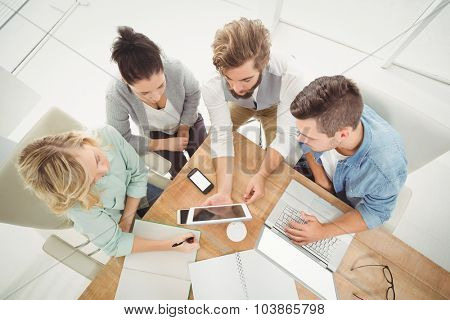 Overhead view of business people with digital tablet while sitting at desk in office