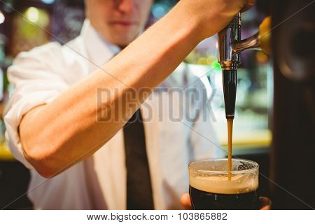 Mid section of barkeeper holding beer glass below dispenser tap at bar counter