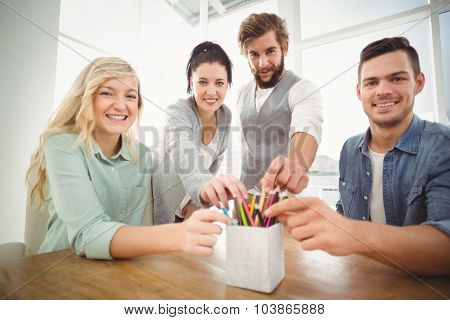 Portrait of smiling business people taking pencils from desk organizer at desk